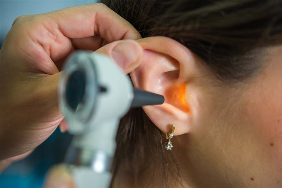 Close-up of a doctor examining a patient's ear with an otoscope