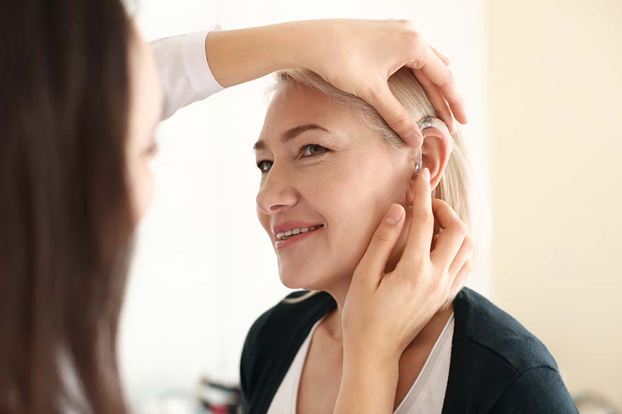 Otolaryngologist putting hearing aid in woman's ear