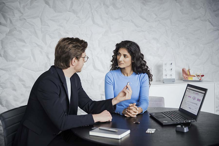 Doctor showing female patient hearing aids