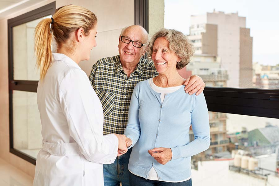 Doctor shaking hands with a female patient speaking with her and her husband