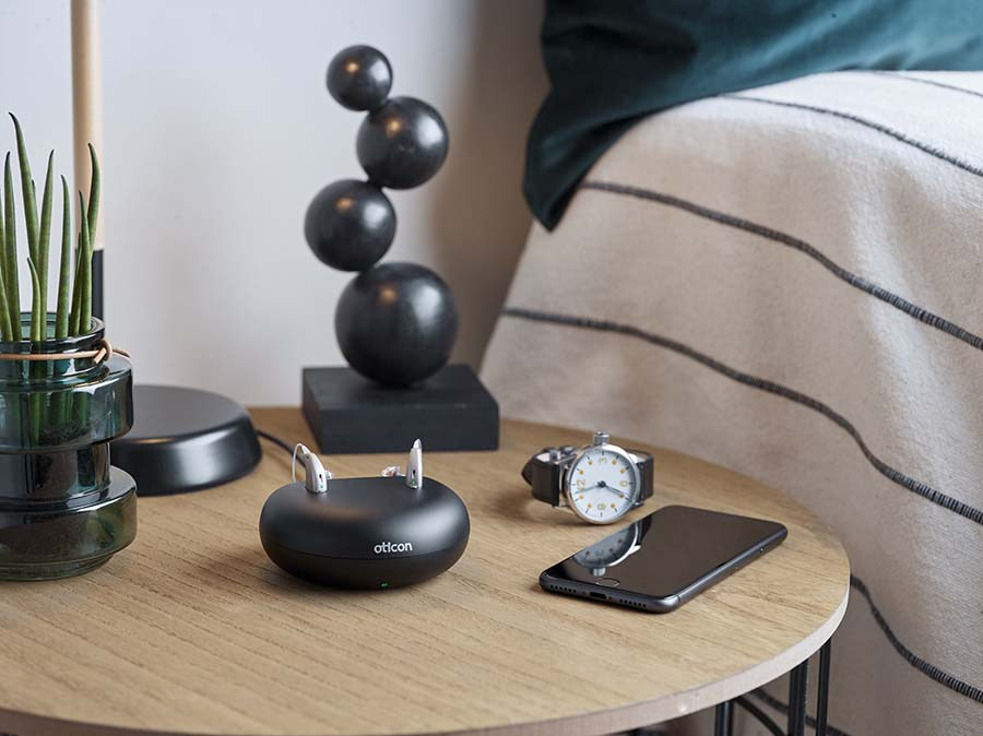 Oticon hearing aids charging on a nightstand