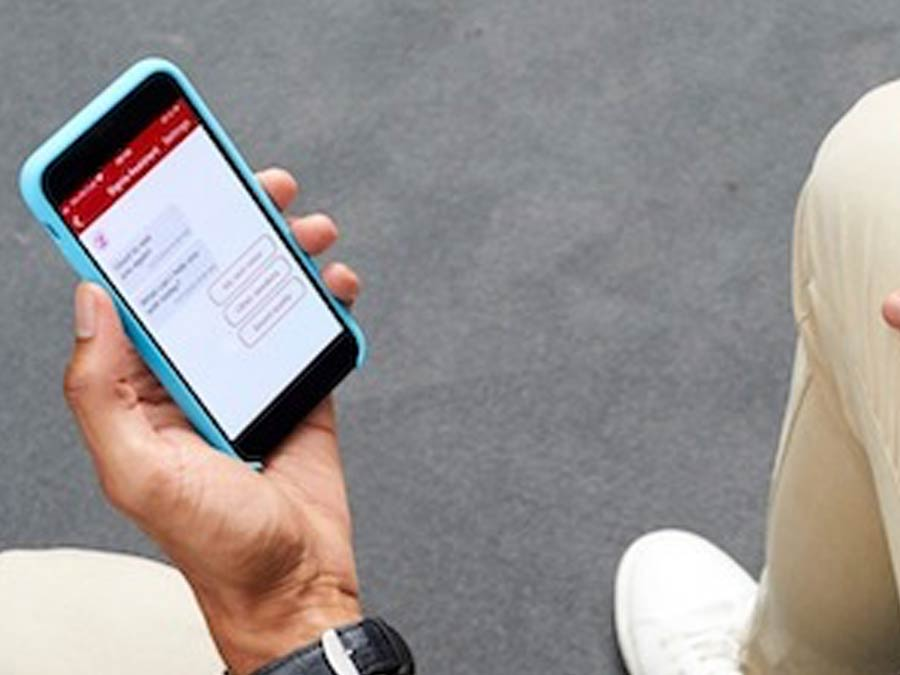 Person holding a smart phone using the Signia Assistant App