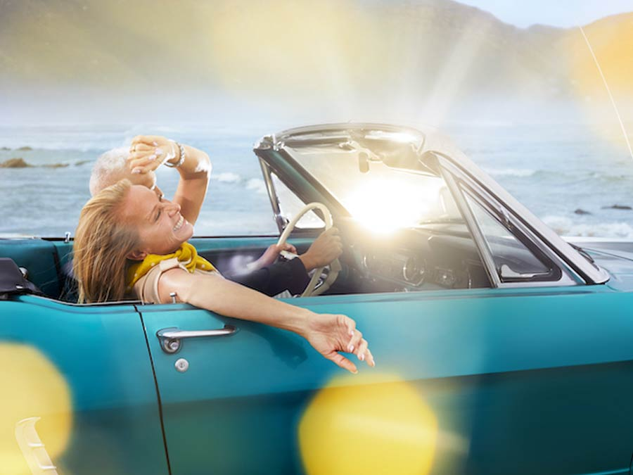 Couple driving in a convertible wearing Signia Styletto X hearing aids