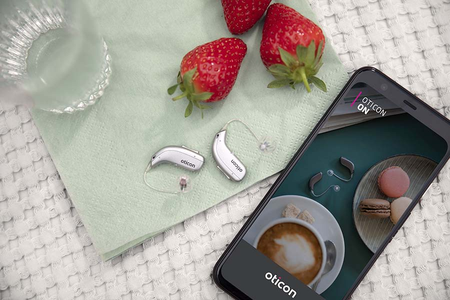 Oticon hearing aids next to a smart phone using the oticon app