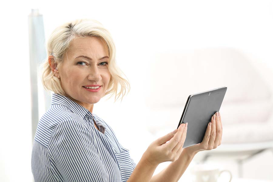 Mature woman with hearing aid using tablet computer indoors