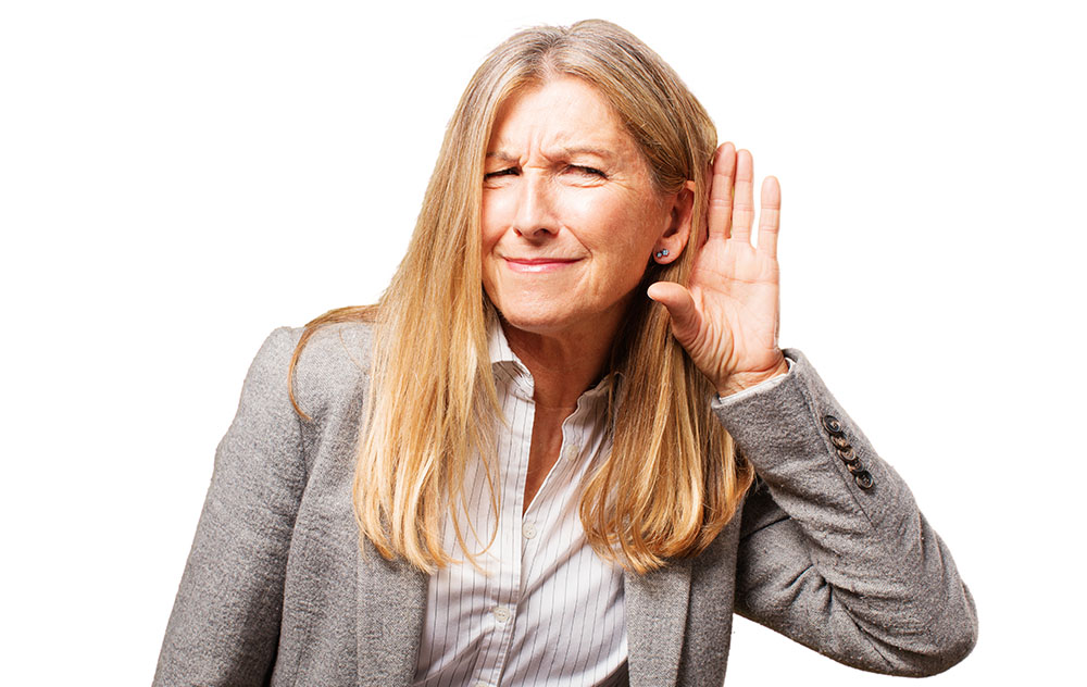 a blonde woman with hearing loss holding her ear