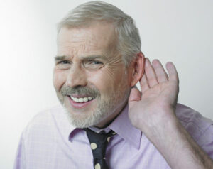 A man with tinnitus holding his ear