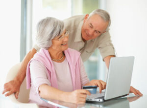 A husband and wife looking at hearing aids on a laptop