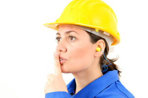 woman in a yellow hardhat and ear plugs